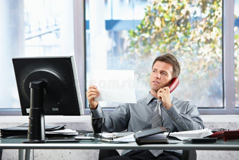 Geschäftsmann beim Aufruf, der Papier betrachtet lizenzfreies stockfoto