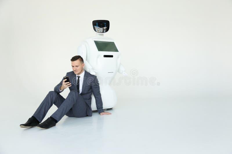 Geschäftsmann benutzt einen Smartphone beim Sitzen auf dem Boden nahe bei einem Roboter Moderne Robotertechnologien humanoid stockbild