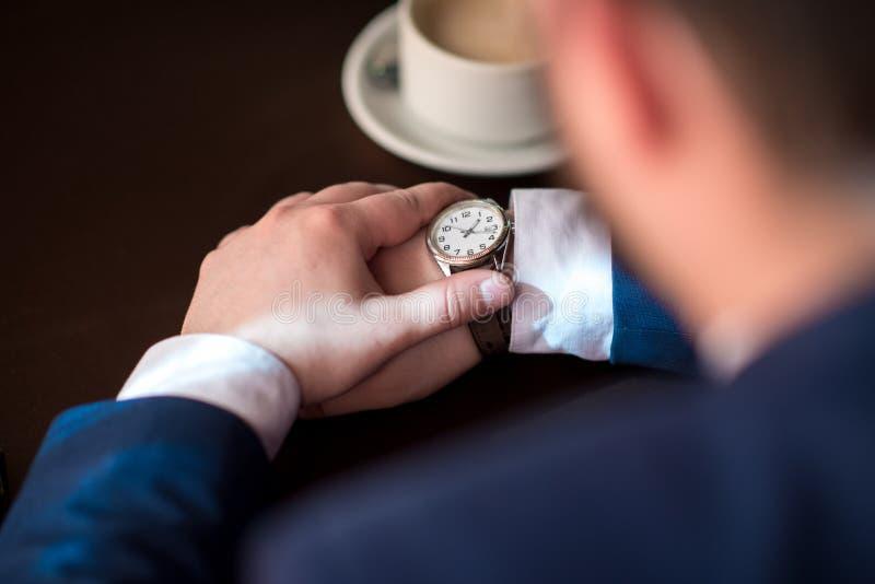 Geschäftsmann betrachtet die Uhr lizenzfreie stockbilder