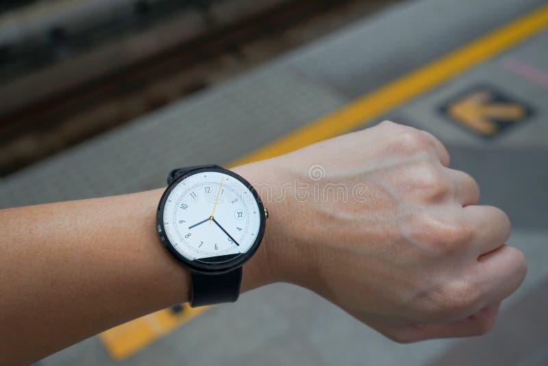 Geschäftsmann-Blick smartwatch Leder-Uhrenarmbänder schwärzen Farbkreisfront auf linker Hand zur U-Bahnplattform-Abendzeit stockfotos