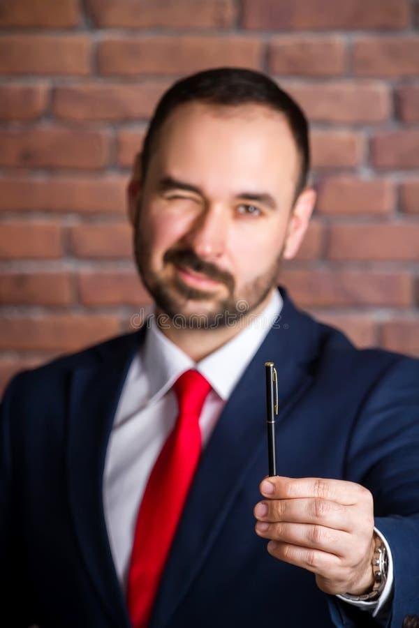 Geschäftsmann blinzelt und bietet an, einen Stift zu nehmen lizenzfreies stockfoto