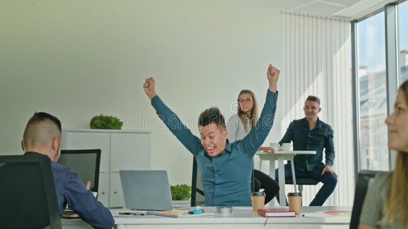 Geschäftsmann Celebrating Victory Looking am Laptop stockfoto
