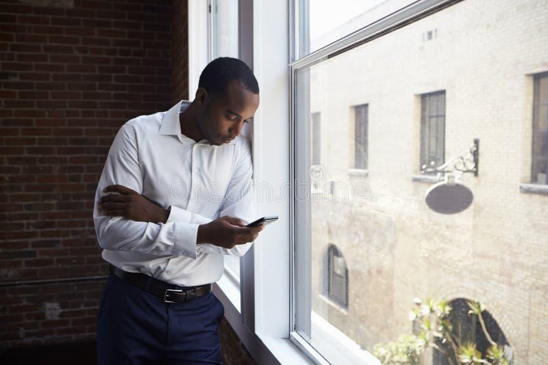 Geschäftsmann Checking Phone Standing durch Büro-Fenster lizenzfreie stockbilder