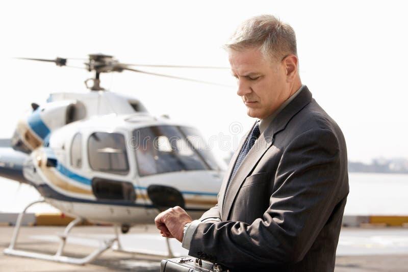 Geschäftsmann Checking Time At die Hubschrauber-Auflage lizenzfreies stockfoto