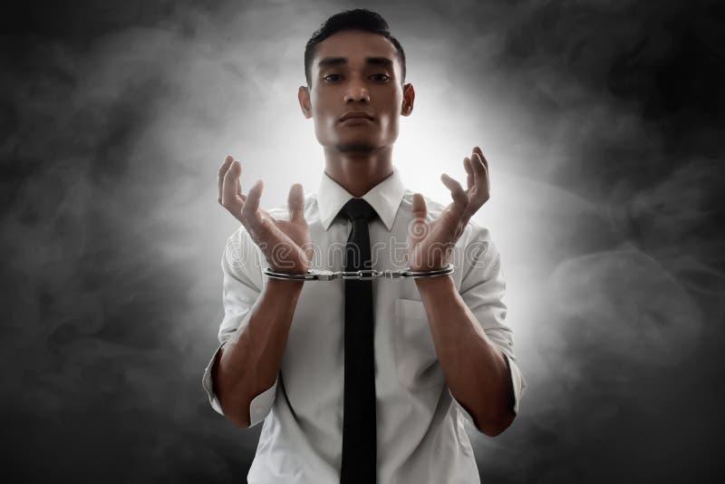 Geschäftsmann in den Handschellen auf Rauchhintergrund stockbilder