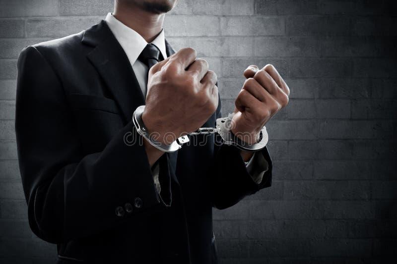 Geschäftsmann in den Handschellen auf Wandhintergrund stockfoto