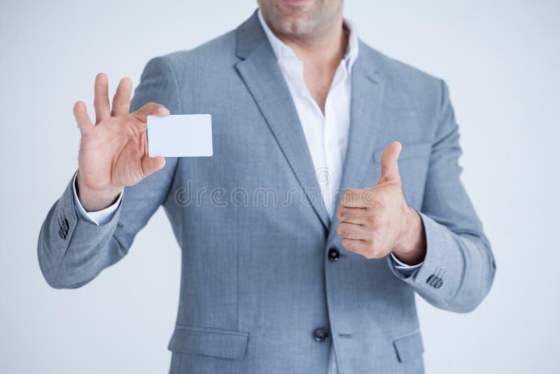 Geschäftsmann in den Klagen zeigen sich Daumen und leeres weißes Kreditkartemodell halten lokalisiert auf weißem Hintergrund mit  stockfoto