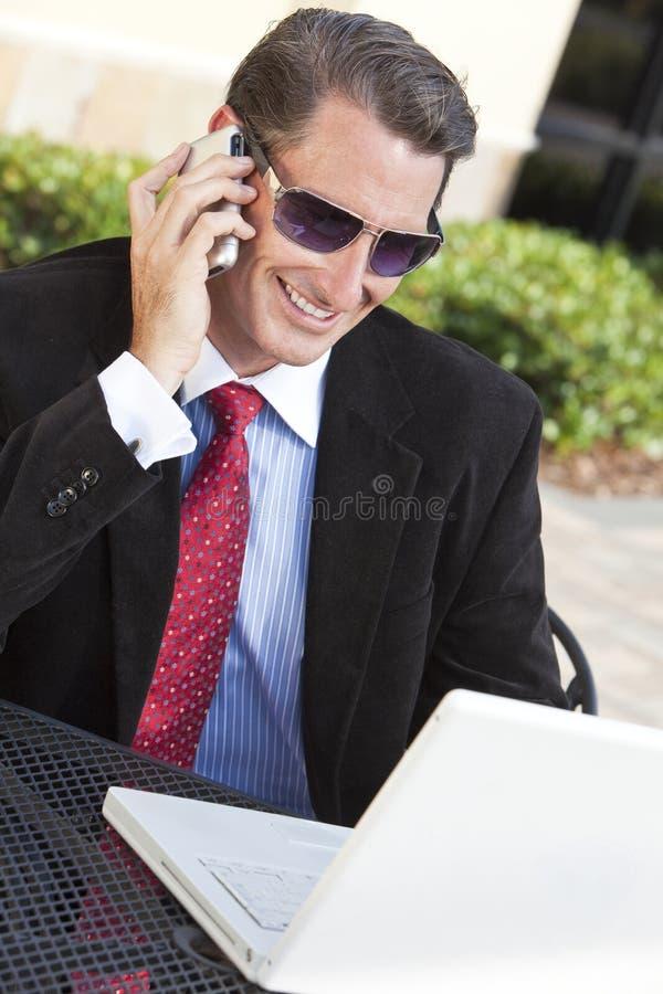 Geschäftsmann in den Sonnenbrillen mit Laptop u. Handy stockfotografie