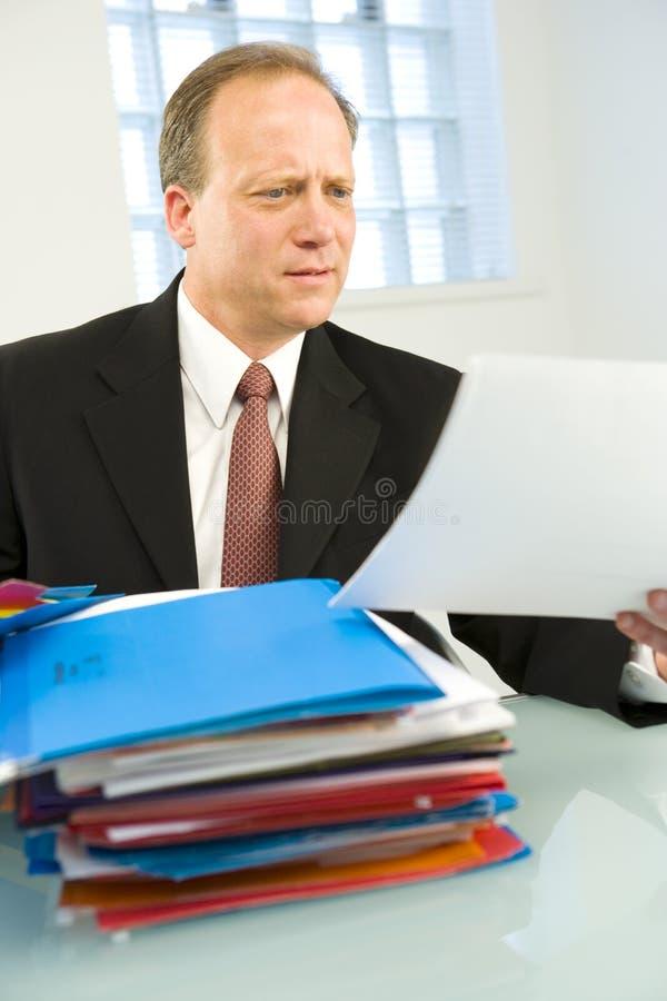 Geschäftsmann, der über Datei schaut lizenzfreies stockbild