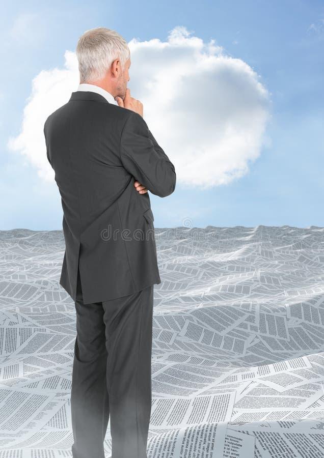 Geschäftsmann, der über Meer von Dokumenten mit Wolke schaut stockfotografie