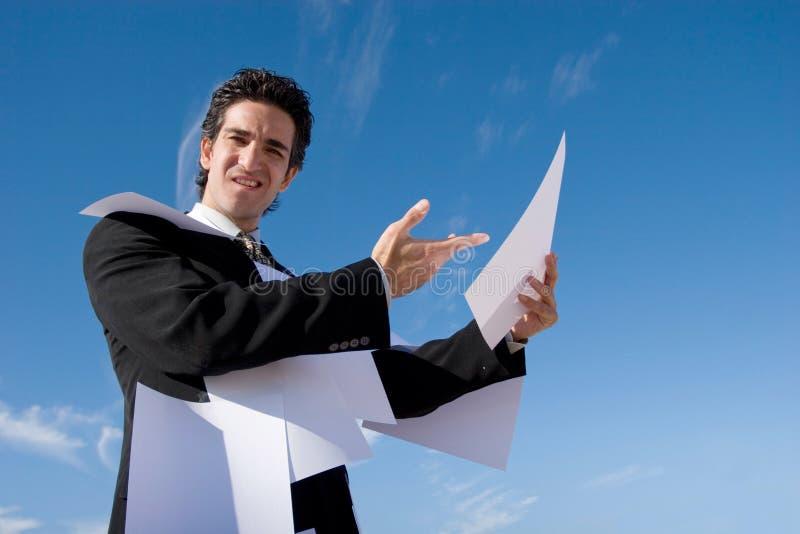 Geschäftsmann, der über Schreibarbeit schaut stockbilder