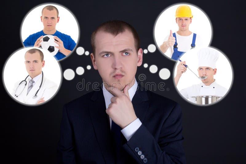 Geschäftsmann, der über seine Zukunft über dunklem BAC denkt oder träumt lizenzfreies stockfoto