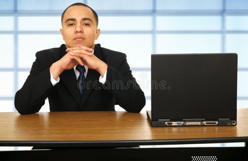Geschäftsmann, der über seinem Laptop denkt lizenzfreie stockfotos