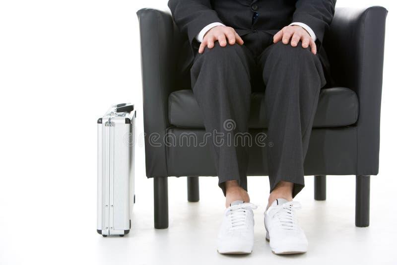 Geschäftsmann, der abnutzende Turnschuhe sitzt stockbild