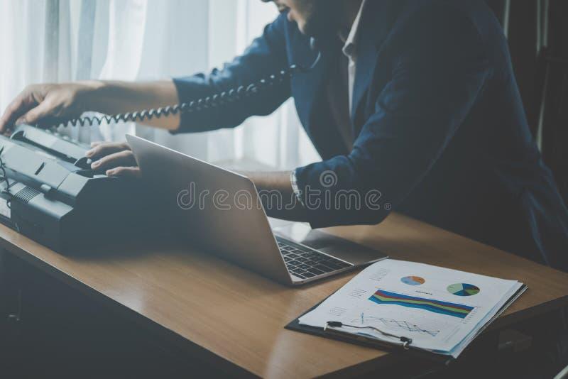 Geschäftsmann, der Anruf auf einem Faxgerät macht stockbild