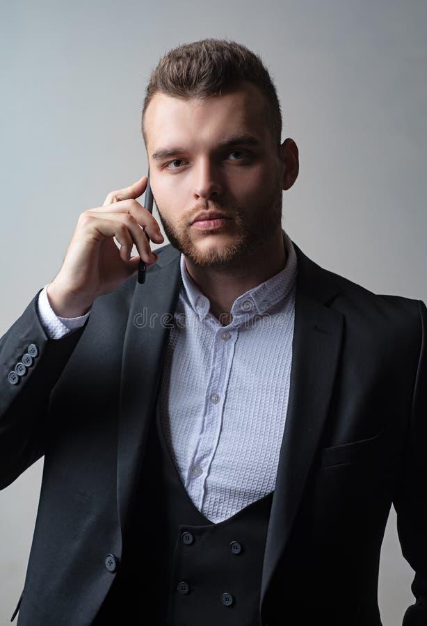 Geschäftsmann in der Arbeit mit Telefon Mobil Klassische Klagen Mannklagenmode Treffen des Telefons stockbild