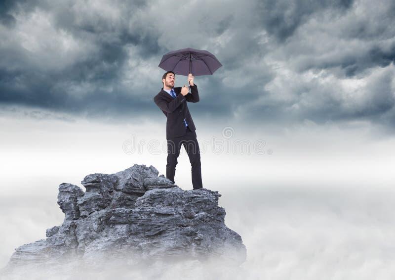 Geschäftsmann, der auf Bergspitze mit Regenschirm gegen stürmische Wolken steht lizenzfreie stockfotografie
