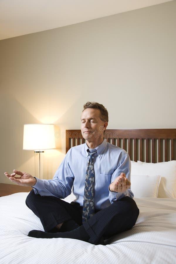 Geschäftsmann, der auf Bett meditiert lizenzfreies stockfoto