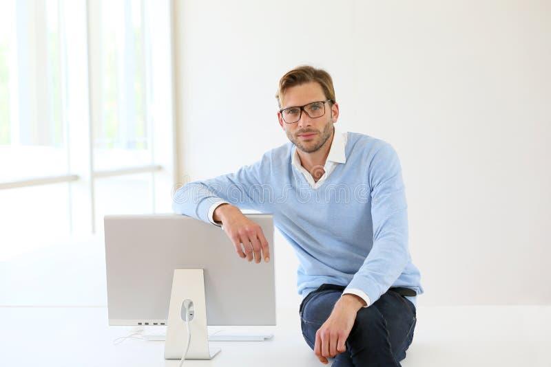 Geschäftsmann, der auf Computer sich lehnt stockfoto