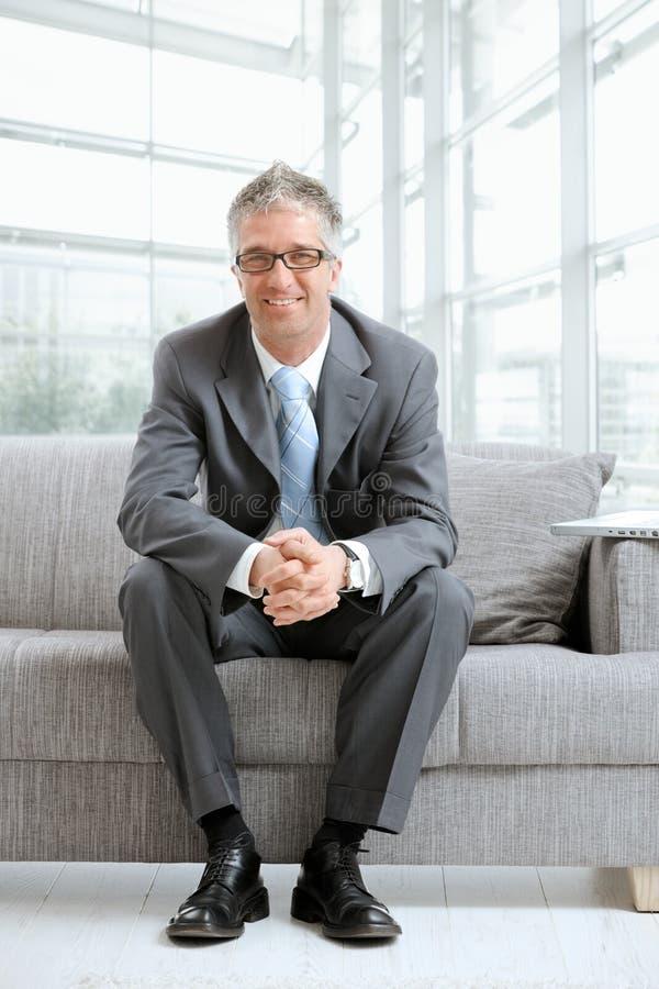 Geschäftsmann, der auf Couch sitzt stockfotos