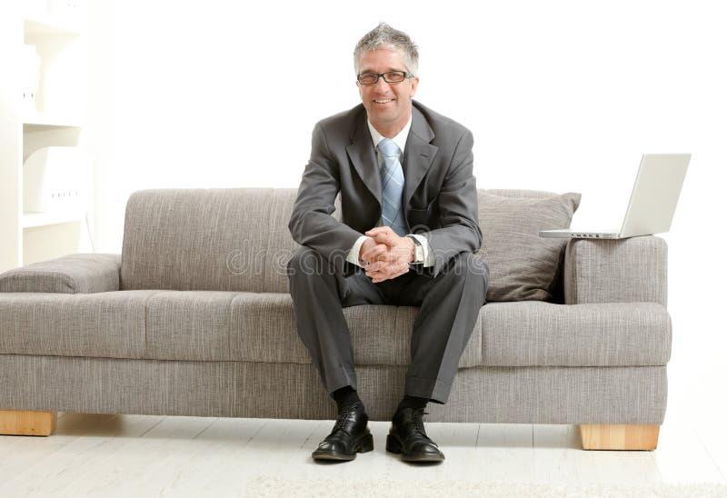 Geschäftsmann, der auf Couch sitzt lizenzfreie stockbilder
