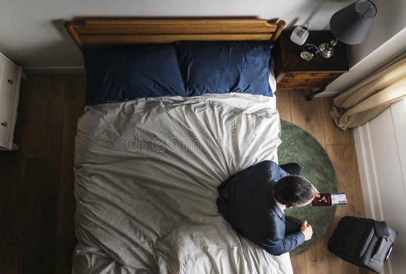 Geschäftsmann, der auf dem Bett unter Verwendung seines Mobiltelefons sitzt lizenzfreies stockfoto
