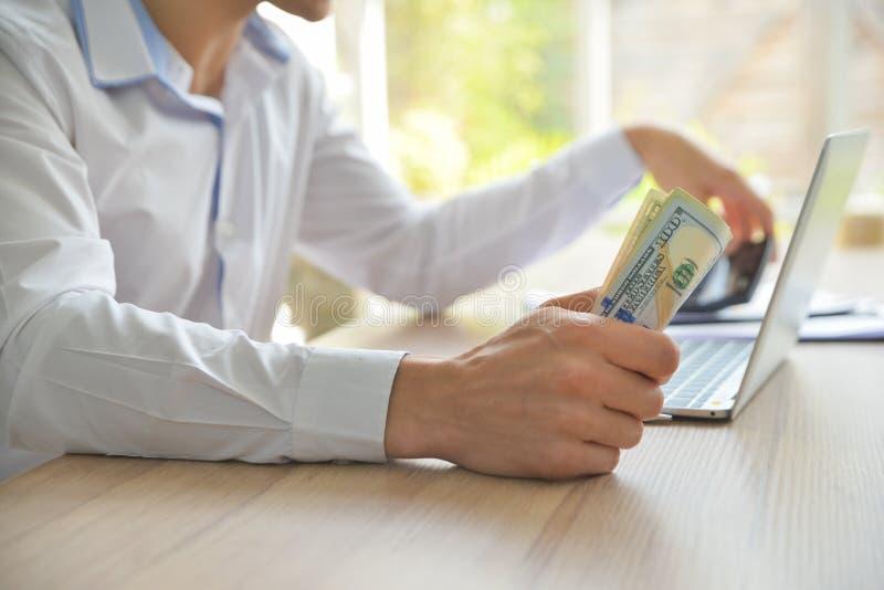 Geschäftsmann, der auf dem Schreibtisch sitzt und Geld in der Hand hält lizenzfreies stockfoto