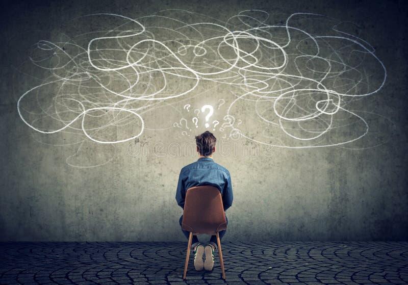 Geschäftsmann, der auf dem Stuhl betrachtet ein Gekritzel auf einem Wandgefühl verwirrt sitzt lizenzfreie stockfotos