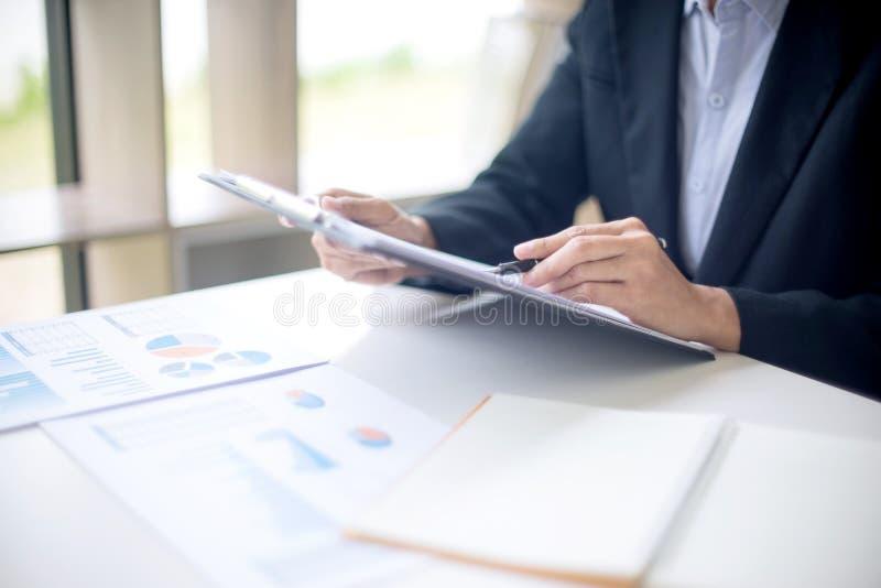 Geschäftsmann, der auf dem Tisch Schreibarbeit seine Hand betrachtet lizenzfreie stockfotos