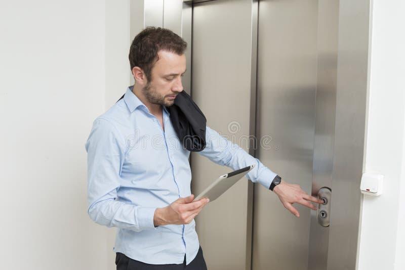 Geschäftsmann, der auf den Aufzug wartet lizenzfreie stockfotografie