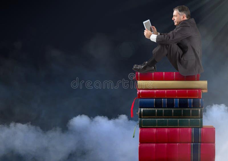 Geschäftsmann, der auf den Büchern gestapelt durch Wolken sitzt stockbild