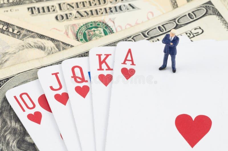 Geschäftsmann, der auf der Glücksspielkarte mit US-Dollar steht lizenzfreies stockbild