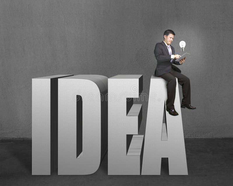 Geschäftsmann, der auf die Oberseite 3D des Wortes IDEE mit Tablette und Glühlampe sitzt lizenzfreie stockfotos