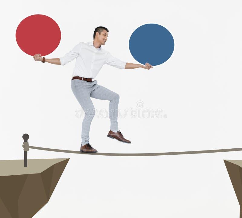 Geschäftsmann, der auf einem einzelnen Seil balanciert stockfotografie