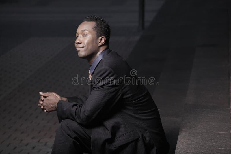 Geschäftsmann, der auf einem Jobstepp nachts sitzt stockfotos