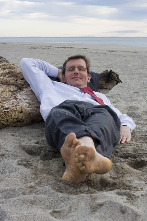Geschäftsmann, der auf einem Strand schläft stockbilder