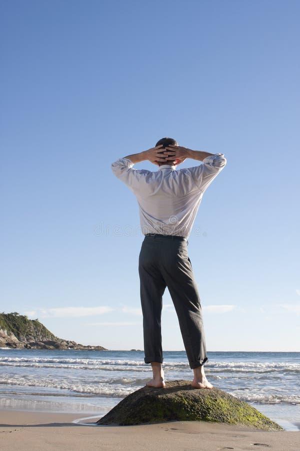 Geschäftsmann, der auf einem Strand sich entspannt lizenzfreies stockfoto