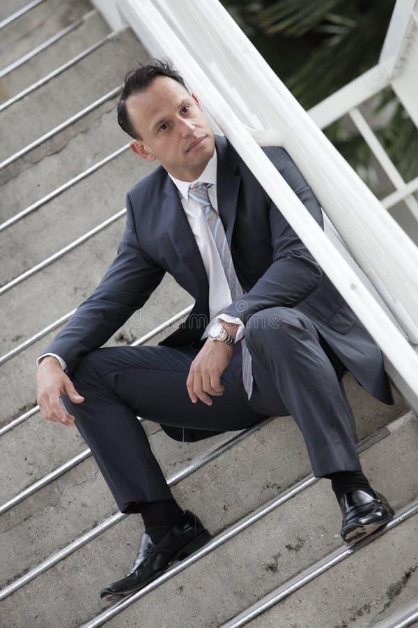 Geschäftsmann, der auf einem Treppenhaus sitzt stockbilder