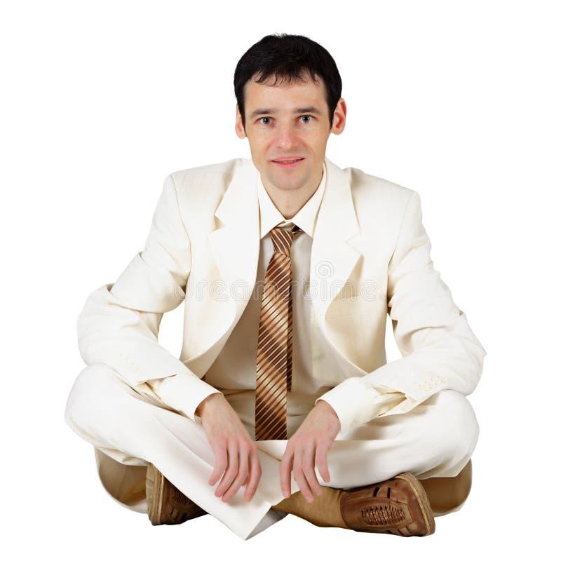 Geschäftsmann, der auf einem Weiß sitzt stockbilder