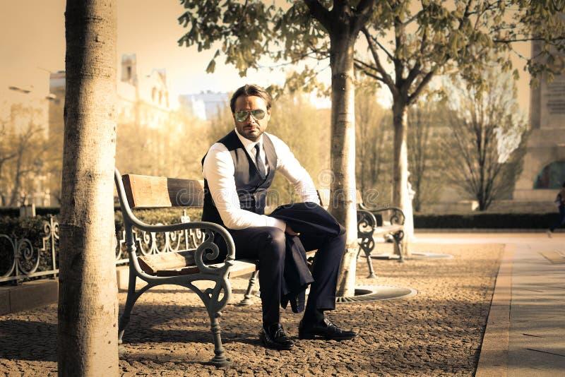 Geschäftsmann, der auf einer Bank sitzt lizenzfreie stockfotografie