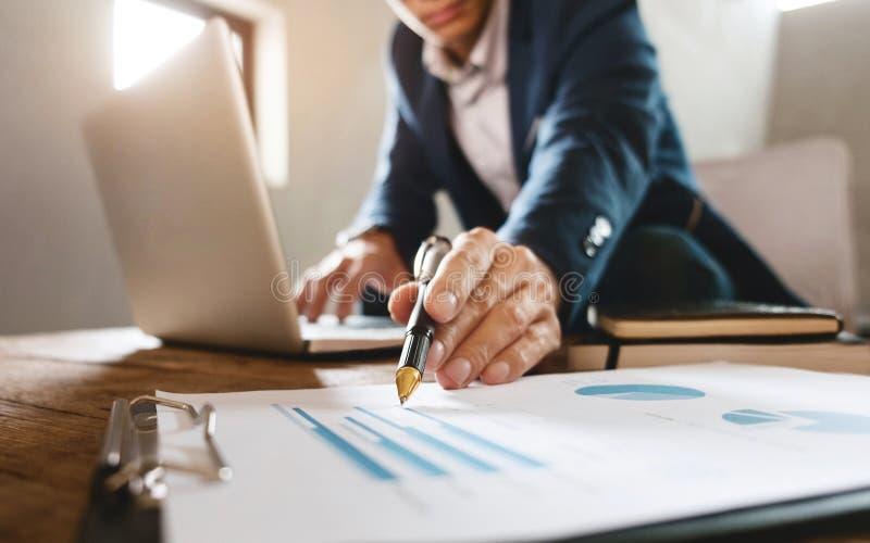Geschäftsmann, der auf Geschäftsdokument mit Laptop auf einen Arbeitsplatz zeigt stockbild