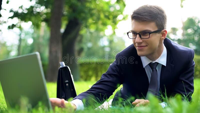 Geschäftsmann, der auf Gras liegt und unter Verwendung des Laptops, beschäftigter Lebensstil, Workaholic simst stockfotografie
