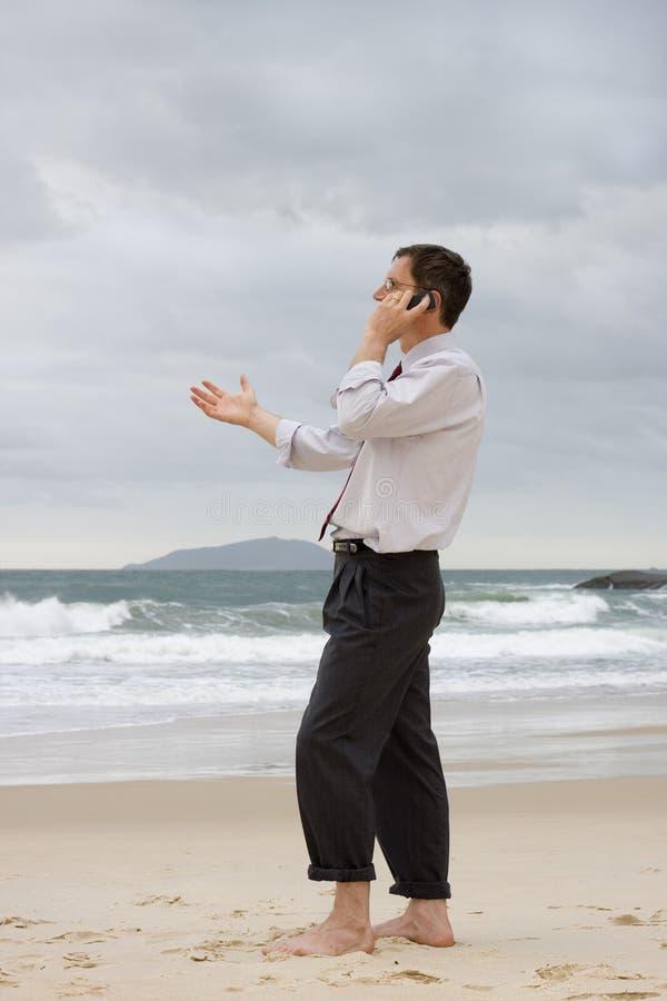 Geschäftsmann, der auf Handy auf einem Strand spricht stockfotografie