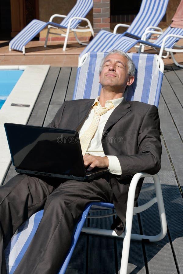 Geschäftsmann, der auf Klappstuhl stillsteht lizenzfreie stockfotos