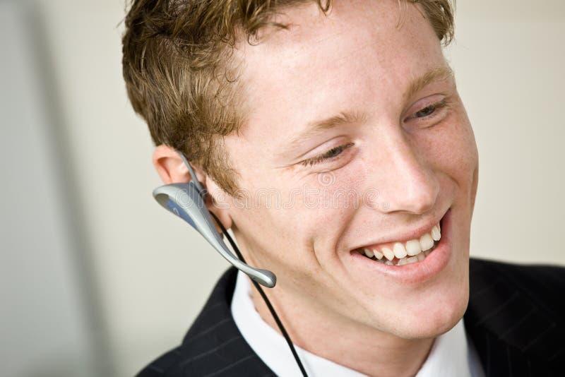 Geschäftsmann, der auf Kopfhörer spricht lizenzfreies stockbild