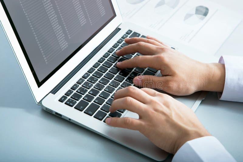 Geschäftsmann, der auf Laptop schreibt stockbild