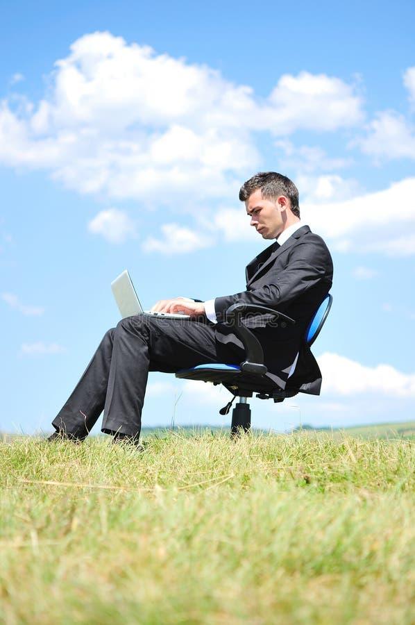 Geschäftsmann, der auf Laptop steht stockbild