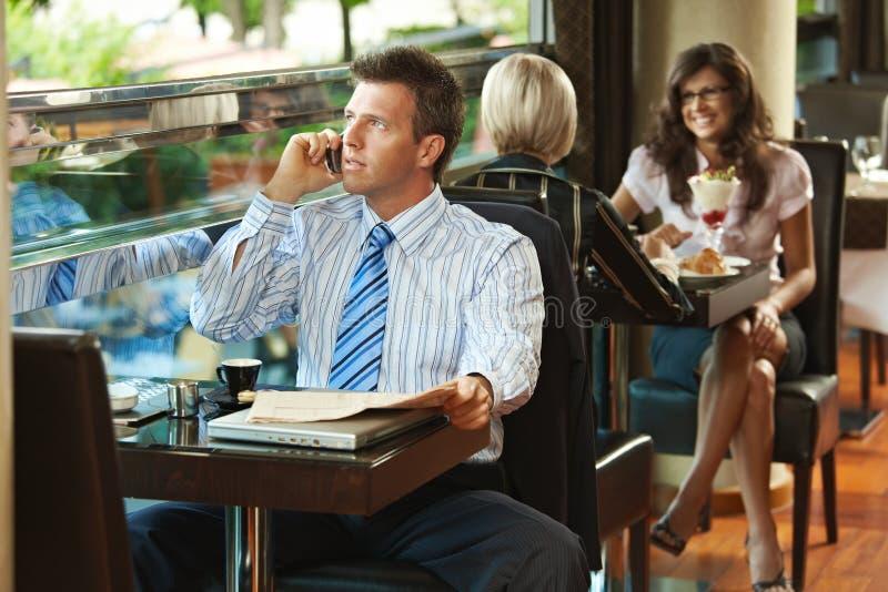 Geschäftsmann, der auf Mobile im Kaffee spricht lizenzfreie stockfotos