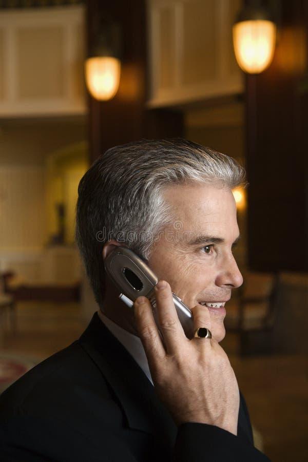 Geschäftsmann, der auf Mobiltelefon in der Hotelvorhalle spricht. stockfoto