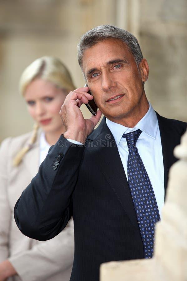 Geschäftsmann, der auf Mobiltelefon spricht stockbild